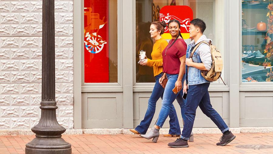 Three people walk past a Wells Fargo branch.