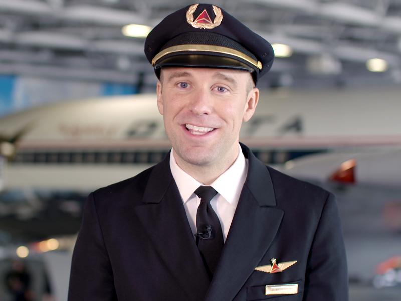 Bren Knoblauch lleva uniforme de piloto de Delta Air Lines y está de pie en un hangar. Hay un avión de Delta en el fondo.